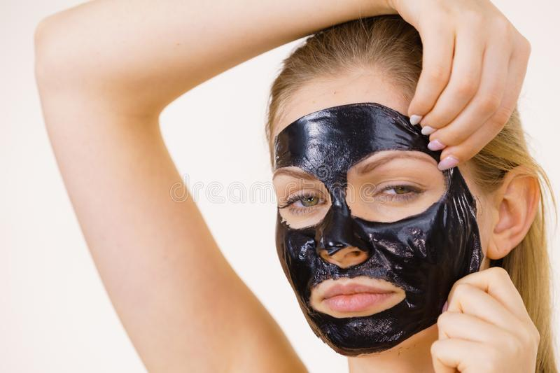 Girl removes black mask from face stock photo