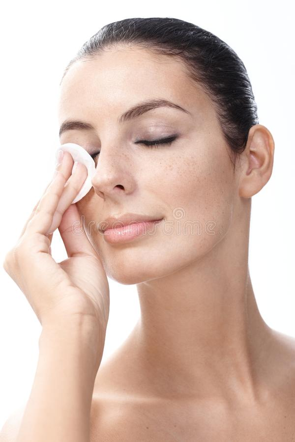Young woman removing eye makeup stock photo