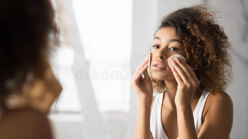 Young Woman Removing Makeup With Cotton Pads In Bathroom, Panorama stock photography