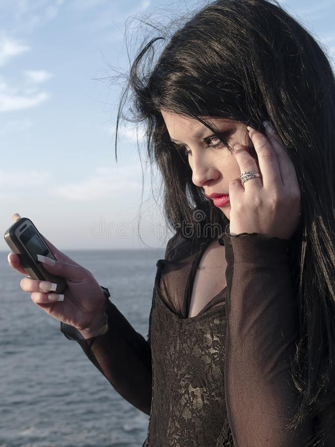 Young woman responding a phone call. Gothic young woman posing outdoors at the seacoast of Valparaiso royalty free stock image