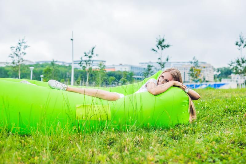 Young woman resting on an air sofa in the park. royalty free stock photography