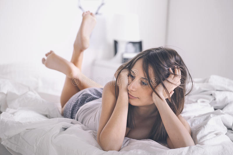 Young woman resting as she lies awake in bed. stock photography