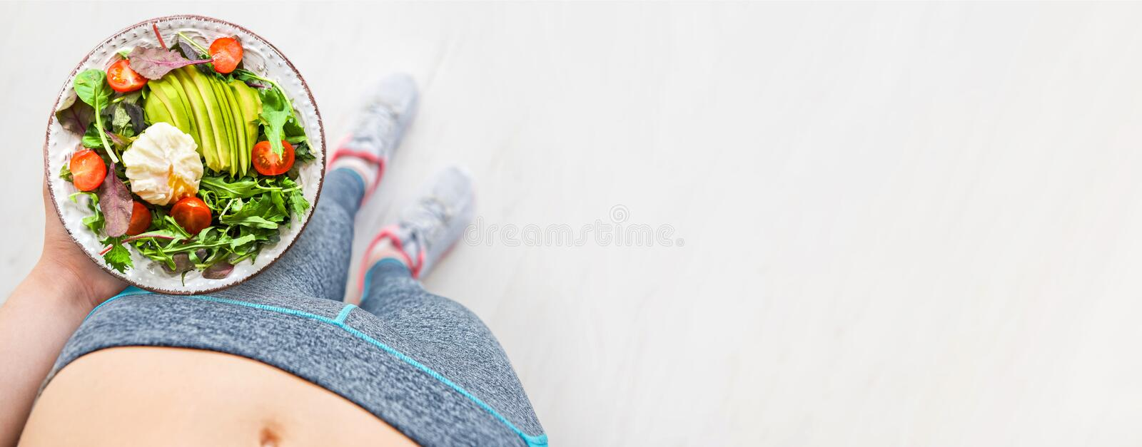 Young woman is resting and eating a healthy food after a workout. royalty free stock photography