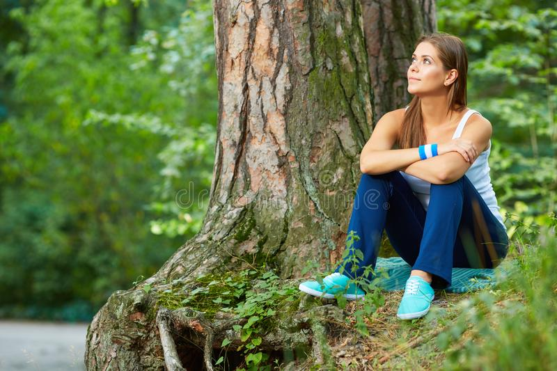 Young woman resting in forest. Green wild wood background. stock photos