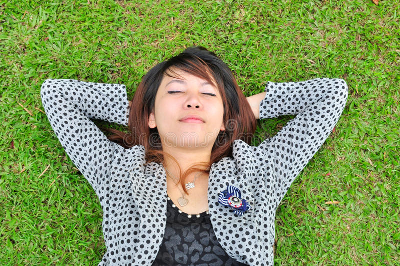Young woman is resting in a green field royalty free stock photo