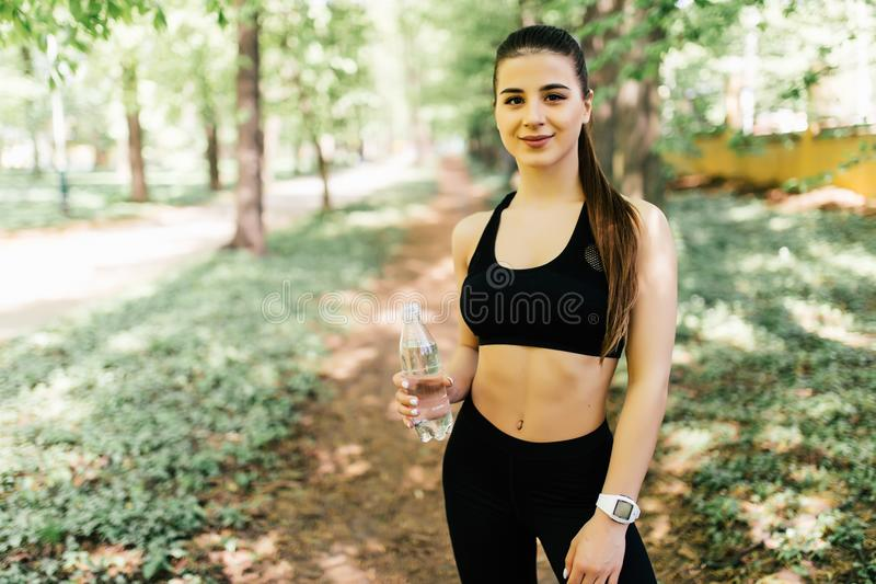 Young woman resting after jogging in park with water to drink stock photos