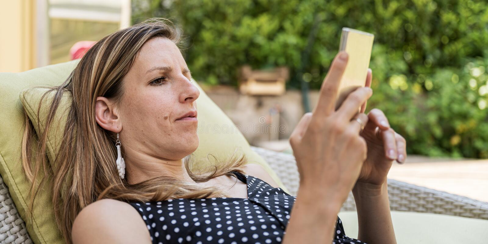 Young woman resting on an outside patio sofa stock photos