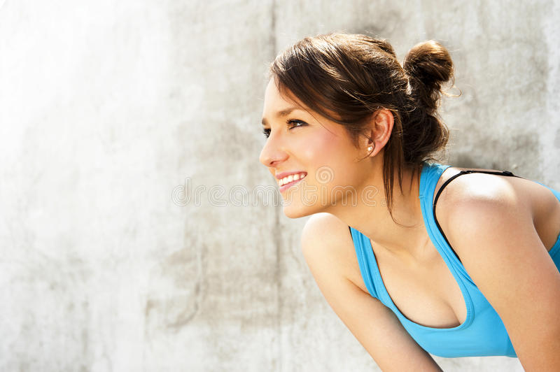 Young woman resting after run by the wall in city with big smile. In blue sportswear royalty free stock image