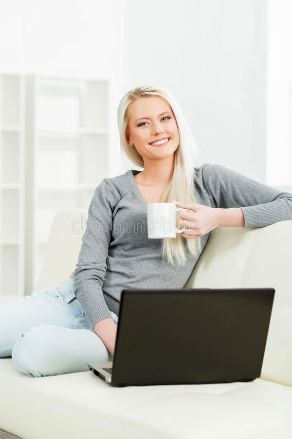 Young woman resting on sofa at home and drinking coffee. Young and happy woman resting on sofa at home and drinking coffee stock photos