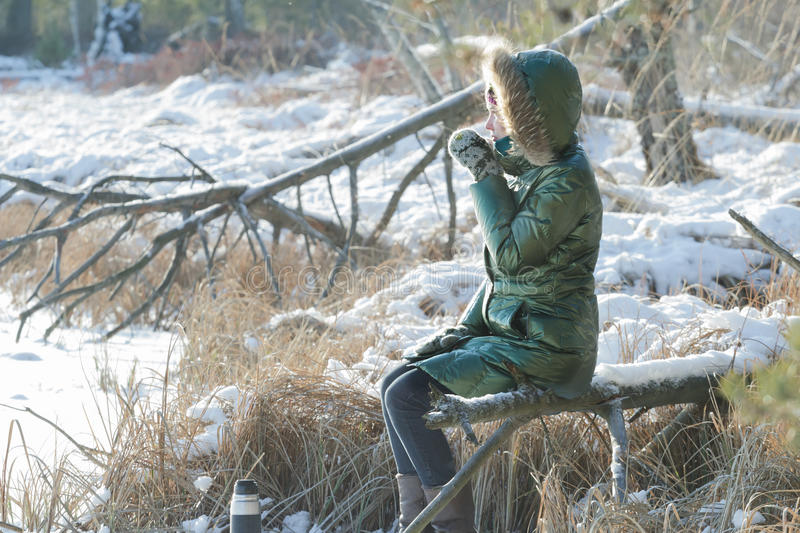 Young woman resting in winter snowy wood with tourist thermos flask outdoors stock photography