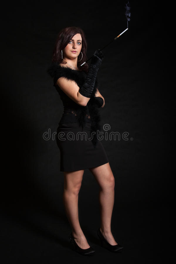 Young woman in retro dress on a black background. Young woman in retro clothing posing with cigarette holder stock photo