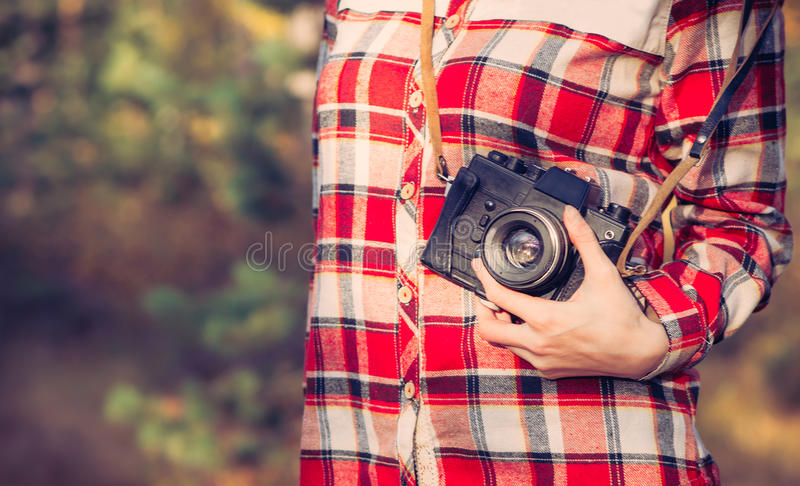 Young Woman with retro photo camera and plaid shirt outdoor royalty free stock image