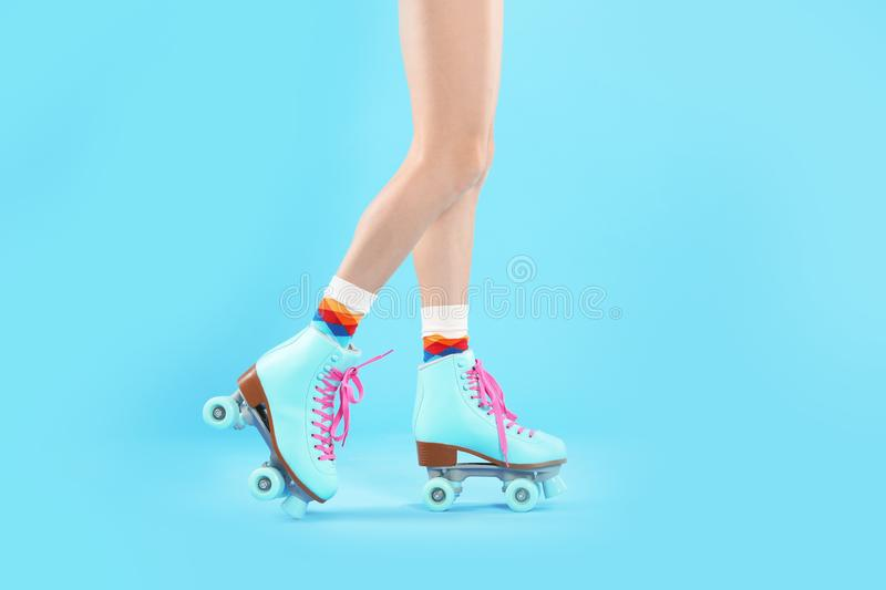 Young woman with retro roller skates on color background. Closeup royalty free stock images