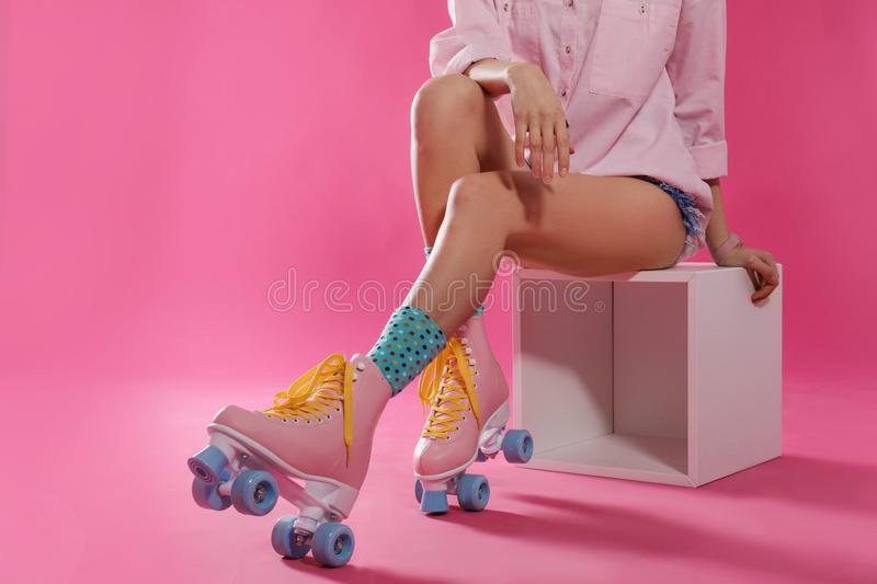 Young woman with retro roller skates on color background, closeup. Space for text royalty free stock images