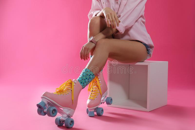 Young woman with retro roller skates on color background, closeup. Space for text stock image