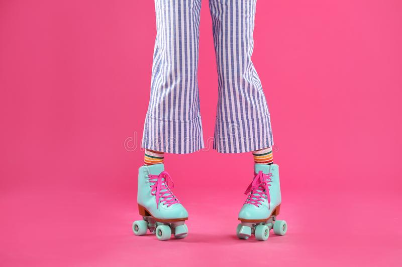 Young woman with retro roller skates on color background. Closeup stock image