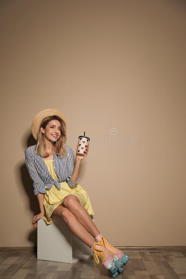 Young woman with retro roller skates and cup of drink against color wall. Space for text stock photography