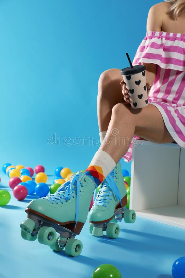 Young woman with retro roller skates and cup of drink on color background, closeup. Space for text royalty free stock photography
