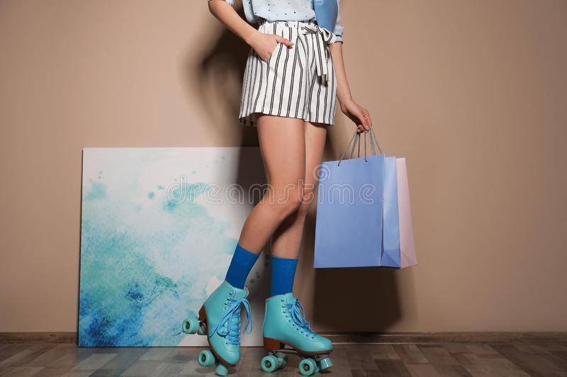 Young woman with retro roller skates and shopping bags against color wall. Closeup stock photos