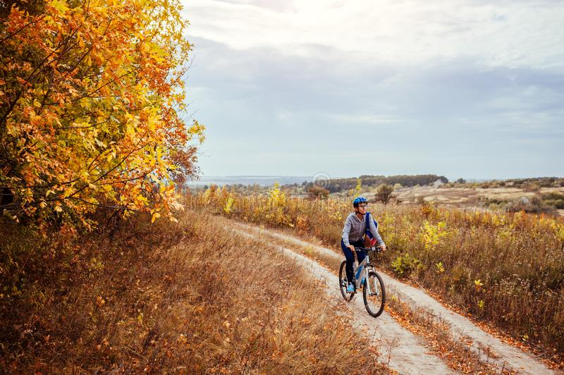 Young woman riding a bicycle in the autumn field stock image