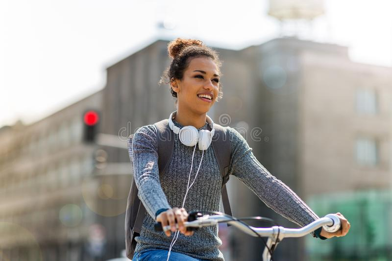 Woman riding bicycle on city street royalty free stock images