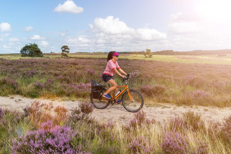 Young woman riding bicycle in the countryside royalty free stock photo