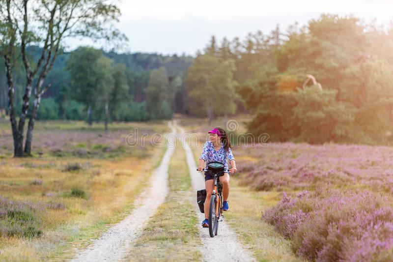 Young woman riding bicycle in the countryside royalty free stock photos
