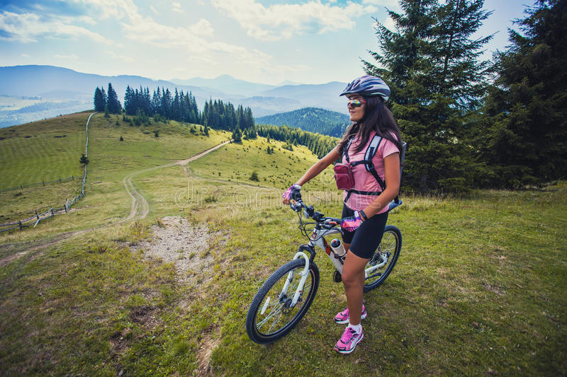 Young woman riding a bicycle on the high plateau stock images