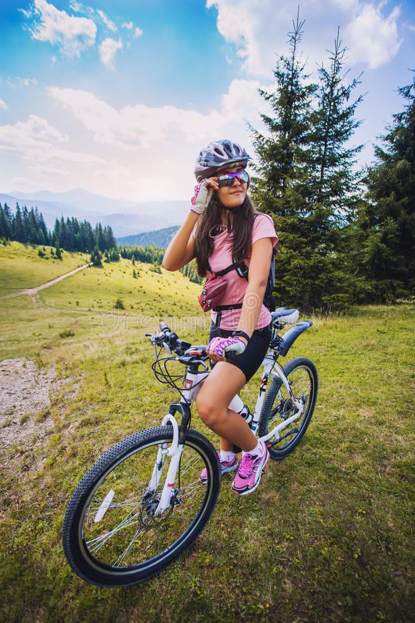 Young woman riding a bicycle on the high plateau stock photo