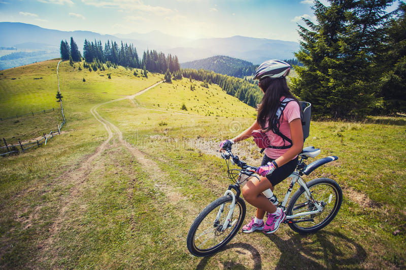 Young woman riding a bicycle on the high plateau stock image