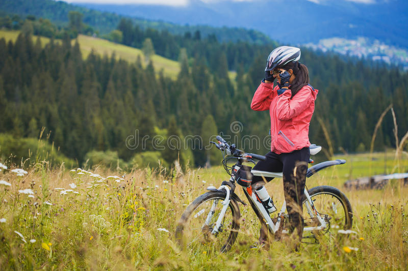 Young woman riding a bicycle on the high plateau royalty free stock photo
