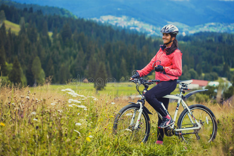 Young woman riding a bicycle on the high plateau royalty free stock image