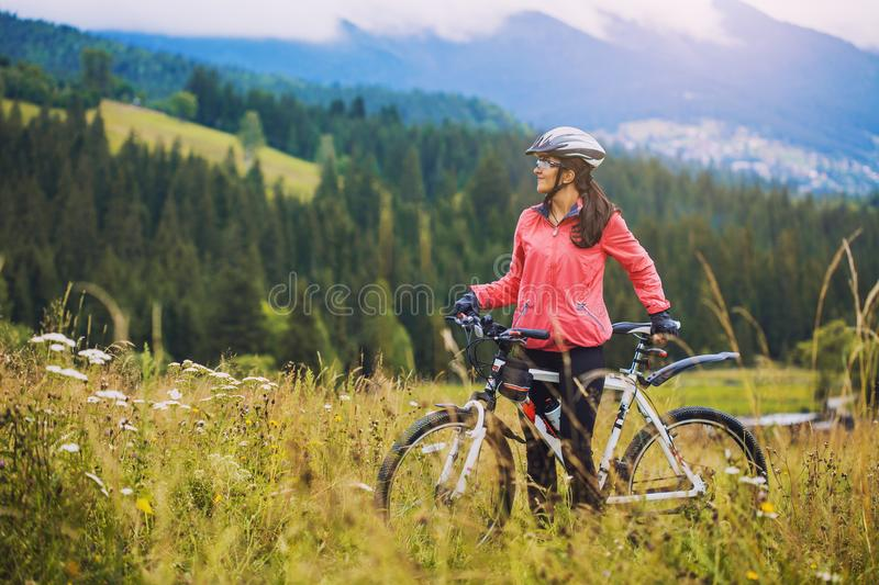 Young woman riding a bicycle on the high plateau royalty free stock images