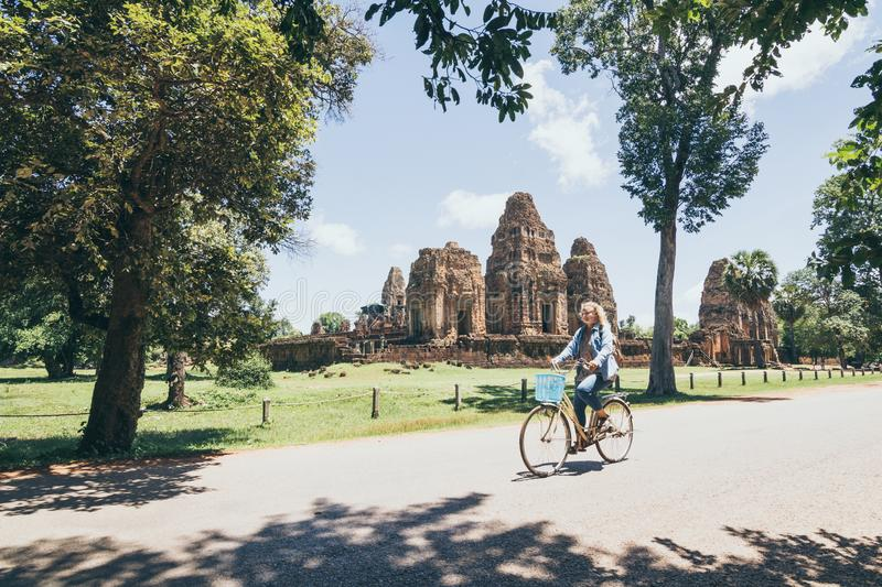 Young woman riding bicycle next to Pre Rup temple in Angkor Wat complex, Cambodia royalty free stock images