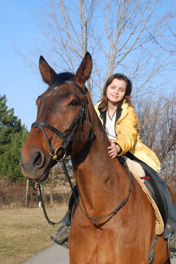 Young woman riding on big brown horse royalty free stock photo
