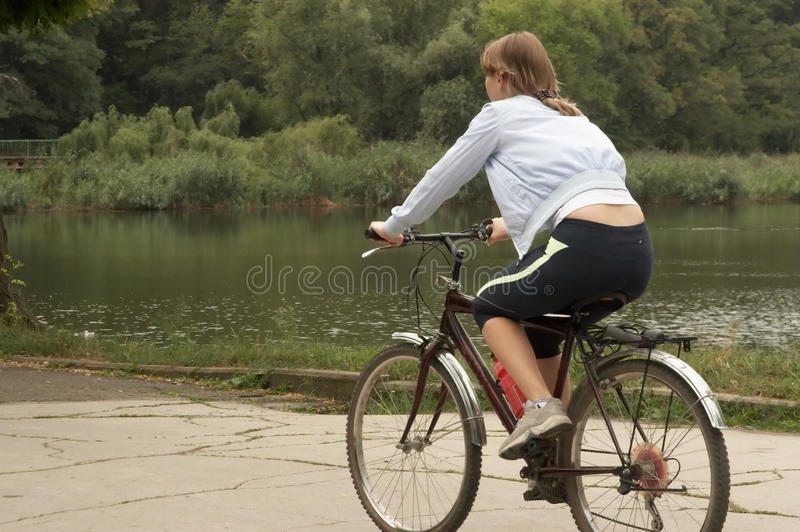 Young woman riding with bike stock image