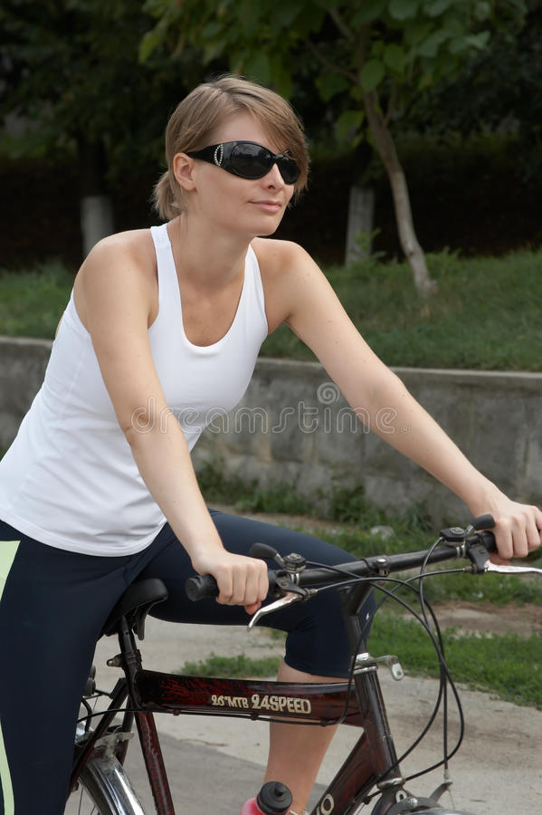 Young woman riding the bike royalty free stock image