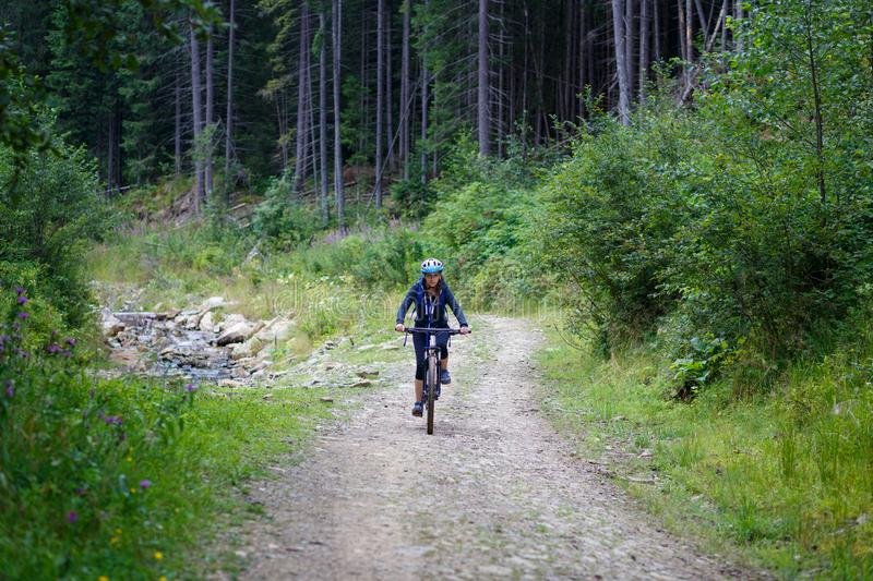 Young woman riding bike on forest trail road royalty free stock photos