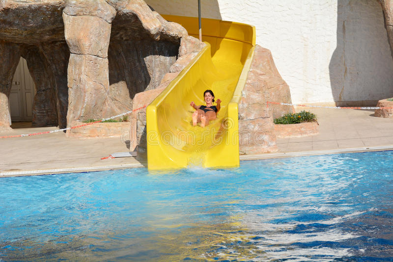 Young woman riding down a water slide-man enjoying a water tube ride. Happy woman coming out a tube ride at the water park and falling into the blue pool with a royalty free stock photography