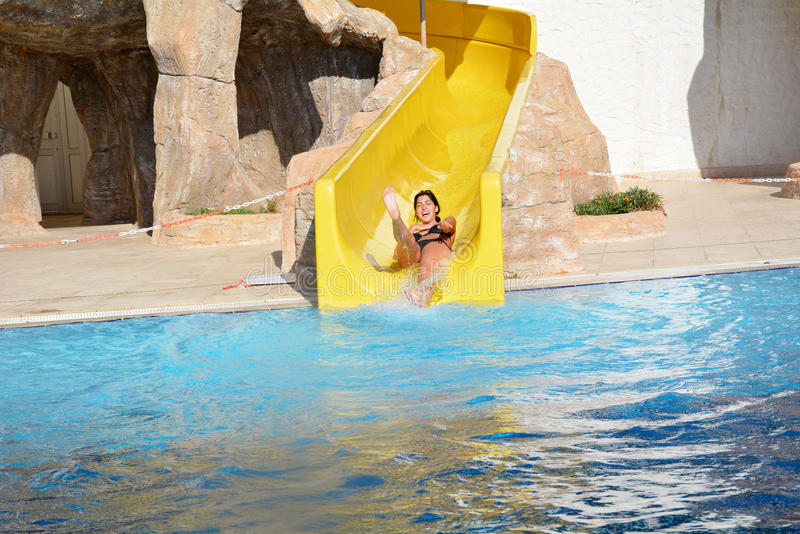 Young woman riding down a water slide-man enjoying a water tube ride. Happy woman coming out a tube ride at the water park and falling into the blue pool with a stock photography