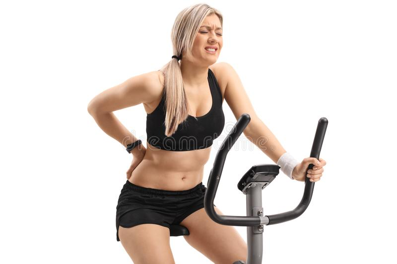 Young woman riding an exercise bike and experiencing back pain. Isolated on white background royalty free stock photo