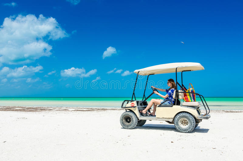 Young girl driving golf cart along tropical beach stock photography