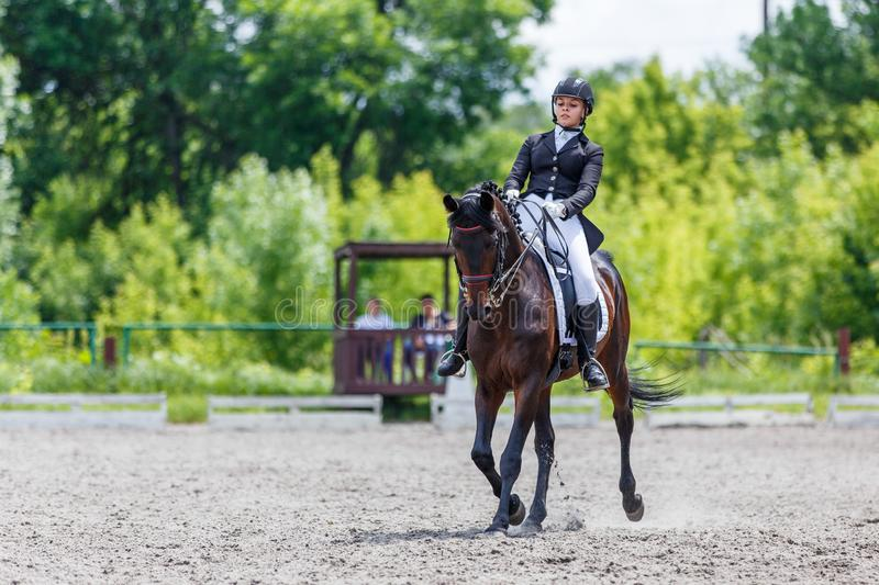 Young woman riding horse on dressage advanced test. Young woman riding horse on equestriansport competition in dressage advanced test stock photography