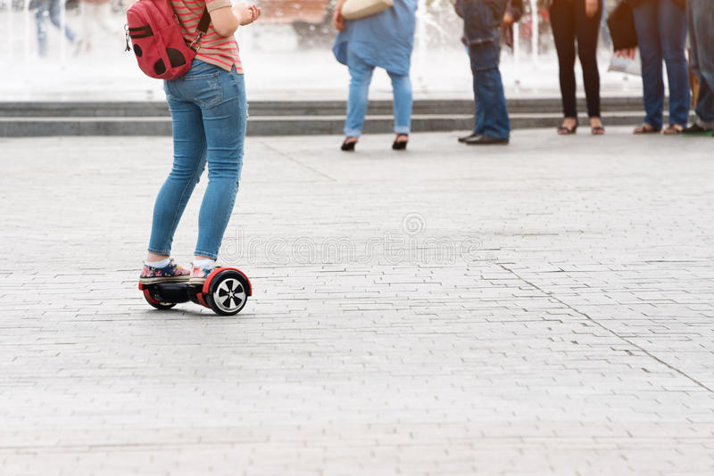 Young woman riding a hoverboard on the city square. New movement and transport technologies. Close up of dual wheel self. Balancing electric skateboard. People royalty free stock photo