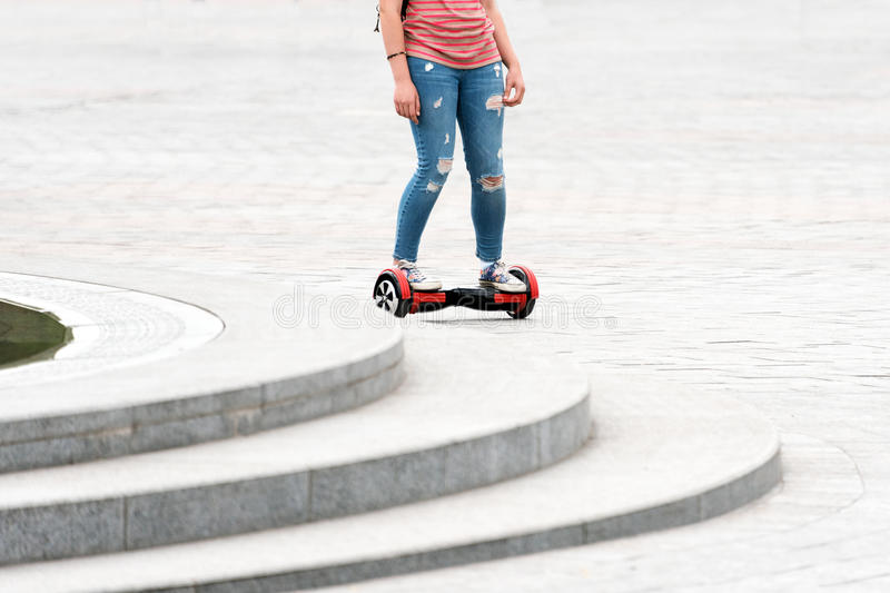 Young woman riding a hoverboard on the city square. New movement and transport technologies. Close up of dual wheel self. Balancing electric skateboard. People royalty free stock photography