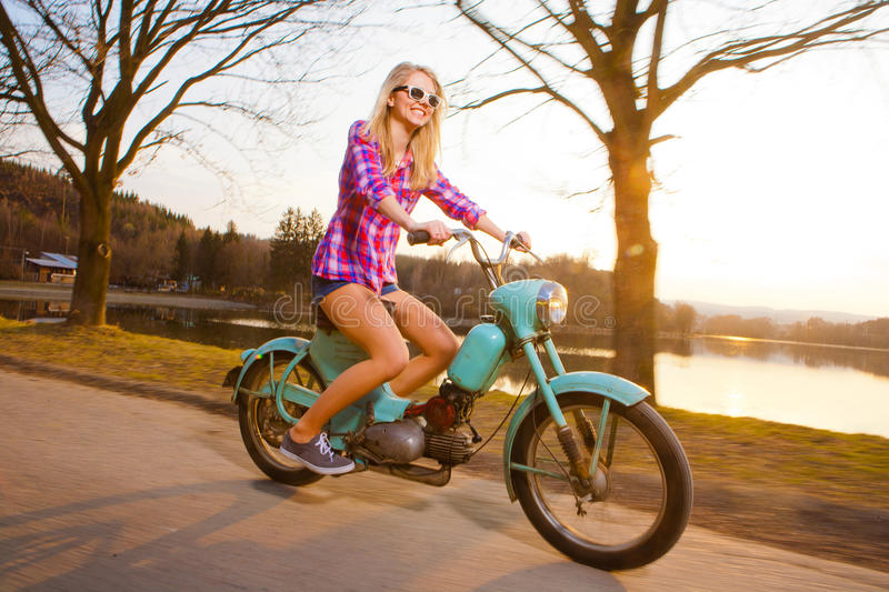 Young woman riding a lifestyle vintage bike. Young beautiful woman riding a lifestyle vintage bike during sunset stock image