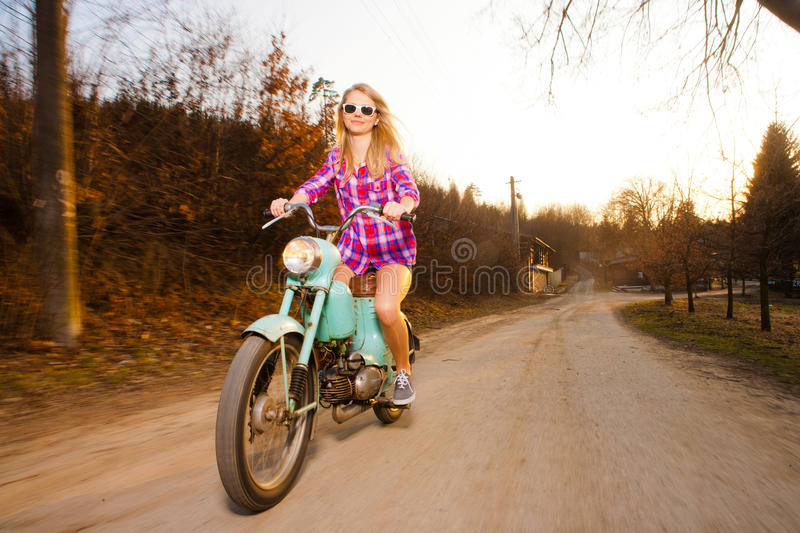Young woman riding a lifestyle vintage bike. Young beautiful woman riding a lifestyle vintage bike during sunset royalty free stock photo
