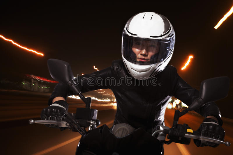 Young woman riding a motorcycle through the streets of Beijing, light trails royalty free stock photos
