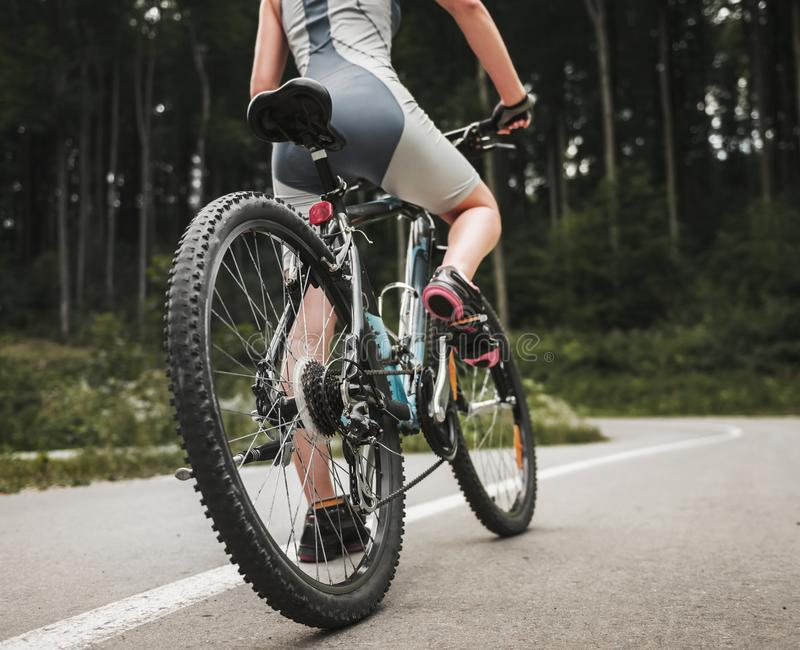 Young Woman Riding on Mountain Bicycle near Forest stock photo