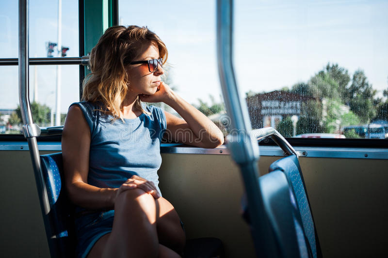 Young woman riding a public bus. On a sunny day stock photo